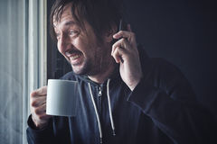 Drinking Coffee And Talking on Mobile Phone in Morning Royalty Free Stock Images