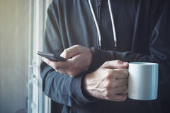 Drinking Coffee And Texting with Mobile Phone in Morning Stock Photos