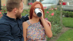 Drinking coffee from to go cup. Young urban people outdoor drinking coffee from to go cup. Couple on park bench with coffee stock video