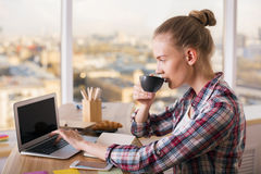 Drinking coffee and using laptop. Casually dressed female enjoying coffee using laptop computer. Hipster woman drinking coffee while waiting for mail on her Royalty Free Stock Photography