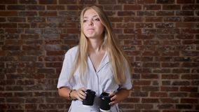Young caucasian blonde girl Listening to music in headphones, dancing, drinking coffee, portrait, brick wall in the stock video
