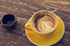 Drinking coffee was decreased to half a cup on wooden table Royalty Free Stock Photos