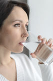 Drinking cool water. Beautiful middle-aged woman drinking water royalty free stock image