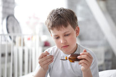 Drinking cough syrup Stock Images