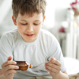 Drinking cough syrup. Boy drinking cough syrup indoors Stock Images