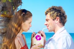 Drinking couple. A portrait of attractive couple having date on the beach Stock Images