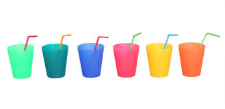 Drinking cups of different colors with straws isolated on white Royalty Free Stock Photos