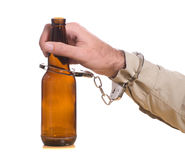 Drinking and Driving. A mans hand is handcuffed to a bottle of beer, isolated against a white background Stock Photo