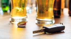 Drinking and driving. Car key on a wooden bar counter. Drinking and driving concept. Car key on a wooden table, pub background Stock Photo