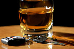 Drinking & Driving - Car Keys & Alcohol. A set of car keys rests in front of a glass of alcohol on a wood bar (shallow focus stock photos