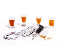Drinking and Driving Enforcement Background. A still life of shot glasses, car keys and police handcuffs against a white background Royalty Free Stock Images