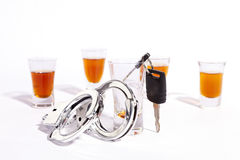 Drinking and Driving Enforcement Background. A still life of shot glasses, car keys and police handcuffs against a white background Royalty Free Stock Photo