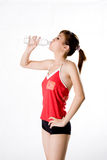 Drinking on exercise break. Woman in between exercise break drinking a bottle of mineral water Stock Images