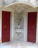 Drinking fountain between two doors. Drinking fountain between two red doors Royalty Free Stock Photography