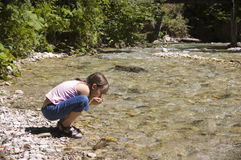 Drinking fresh Water. Girl drinking from a clear Austrian River Stock Images
