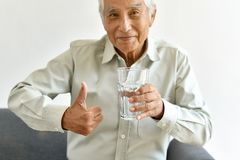 Drinking fresh water is good healthy habit for old man, Elderly smiling asian man show thumb up to glass of purified water. royalty free stock images