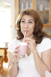 Drinking Fruit Drink. Woman drinking a fruit smoothie through a straw in kitchen setting looking up Royalty Free Stock Photography