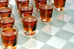 Drinking game. Wineglasses as chess figures on a glass chessboard royalty free stock photos