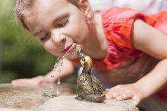 Drinking girl. Little girl drinking from a water fountain Stock Image