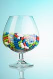Drinking glass with drug pills Stock Photos