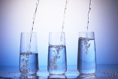 Drinking glasses with reflection in drops. Water pouring stock image