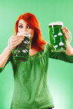 Drinking green beer for St Patricks Day. Photo of a beautiful redhead woman holding and drinking two huge green beers Stock Photography