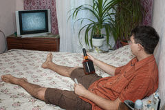 Drinking at home. Guy in bed with bottle of whiskey watching tv stock image