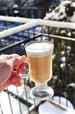 Hot drink cold winter outside. Drinking coffee cuppacino . action of hand holding glass outside in sunshine. hot cold contrast Royalty Free Stock Images