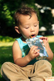 Drinking Juice. Toddler sitting down on grass in park having a drink from a juice pack Royalty Free Stock Image