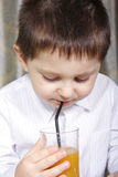 Drinking juice. Boy drinking juice weared in a white shirt holding glass in hand Stock Images