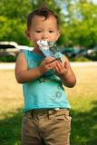 Drinking Juice Standing Up. Young toddler standing outside in park drinking from juice pack on sunny day Royalty Free Stock Images