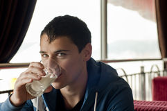 Drinking milk. Young smiling man drinking milk Royalty Free Stock Photos