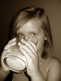 Drinking milk. Little girl drinking a big glass of milk.  Sepia tone Stock Photo