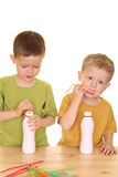 Drinking milk/jogurt. Five and three years old boys drinking milk isolated on white royalty free stock photos