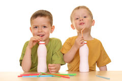 Drinking milk/jogurt. Five and three years old boys drinking milk isolated on white Royalty Free Stock Photography