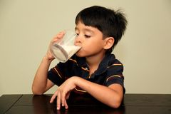 Drinking milk. A little boy drinking fresh milk from a glass Royalty Free Stock Photography