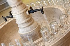 Drinking Mineral Water from an Antique tap/faucet. Free Drinking Mineral Water from an Antique tap/faucet in Europe, with glasses provided stock photos