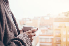 Man is drinking coffee on a balcony. Close up of hands with white cup of coffee. Early morning routine Stock Photos