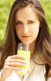 Drinking orange juice. Young girl holding glass of orange juice Royalty Free Stock Image