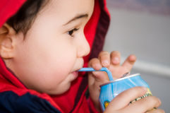 Drinking orange juice. Cute little boy (4 years old) is drinking orange lemonade Royalty Free Stock Photography
