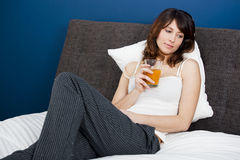 Drinking orange juice on bed Stock Images