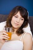 Drinking orange juice on bed Stock Image