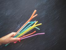 Drinking paper colorful straws in hand for summer cocktails on dark background with copy space. Top view. Group of objects stock images