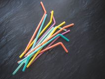 Drinking paper colorful straws for summer cocktails on dark background with copy space. Top view. Group of objects royalty free stock image