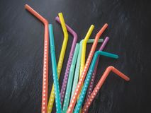 Drinking paper colorful straws for summer cocktails on dark background with copy space. Top view. Group of objects royalty free stock photography