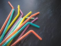 Drinking paper colorful straws for summer cocktails on dark background with copy space. Top view. Group of objects stock images