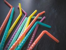 Drinking paper colorful straws for summer cocktails on dark background with copy space. Top view. Group of objects royalty free stock photo