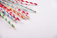 Drinking paper colorful straws for summer cocktails on white background with copy space. Top view. Drinking paper colorful straws for summer cocktails on white stock images