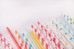 Drinking paper colorful straws for summer cocktails on white background with copy space. Top view. Drinking paper colorful straws for summer cocktails on white royalty free stock photos