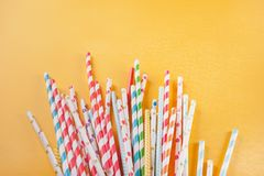 Drinking paper colorful straws for summer cocktails on yellow background with copy space. Top view. Drinking paper colorful straws for summer cocktails on yellow stock image